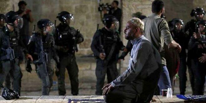 Seorang Muslim Palestina salat di tengah penjagaan polisi Israel