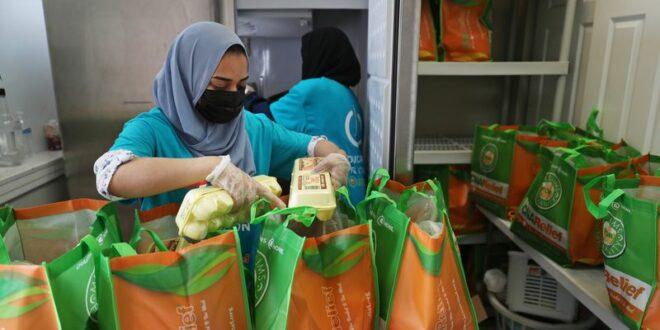 Relawan Safeera Khan memasukan makanan dan daging halal ke kantung kantung yang akan dibagikan kepada keluarga yang membutuhkan