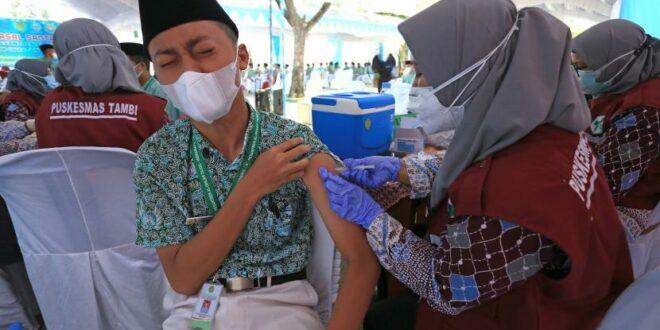 petugas kesehatan menyuntikkan vaksin covid kepada santri di pondok